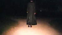 Girl In A Black Cloak Walking On A Footpath At Night